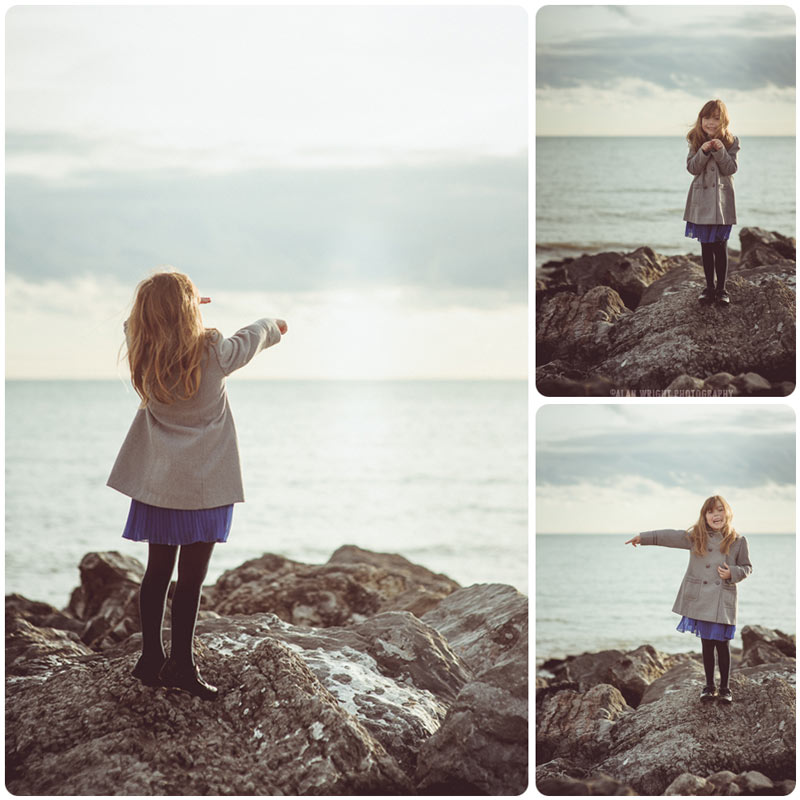 Child stands and poses comically on rocks at the beach