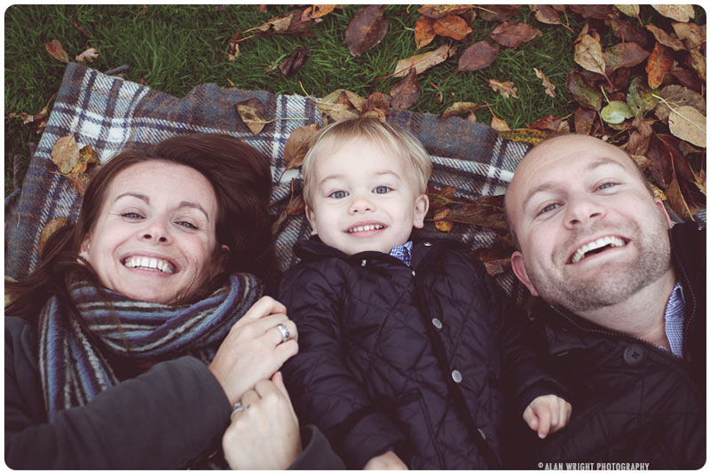 A family enjoys playing with the autumnal leaves