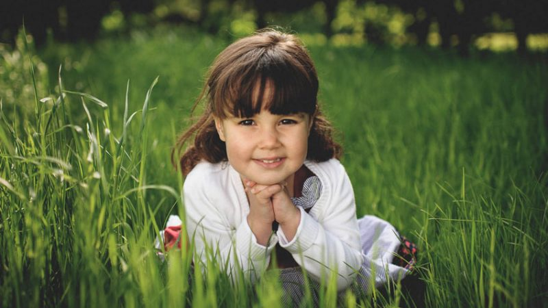 Child poses for photo in long green grass