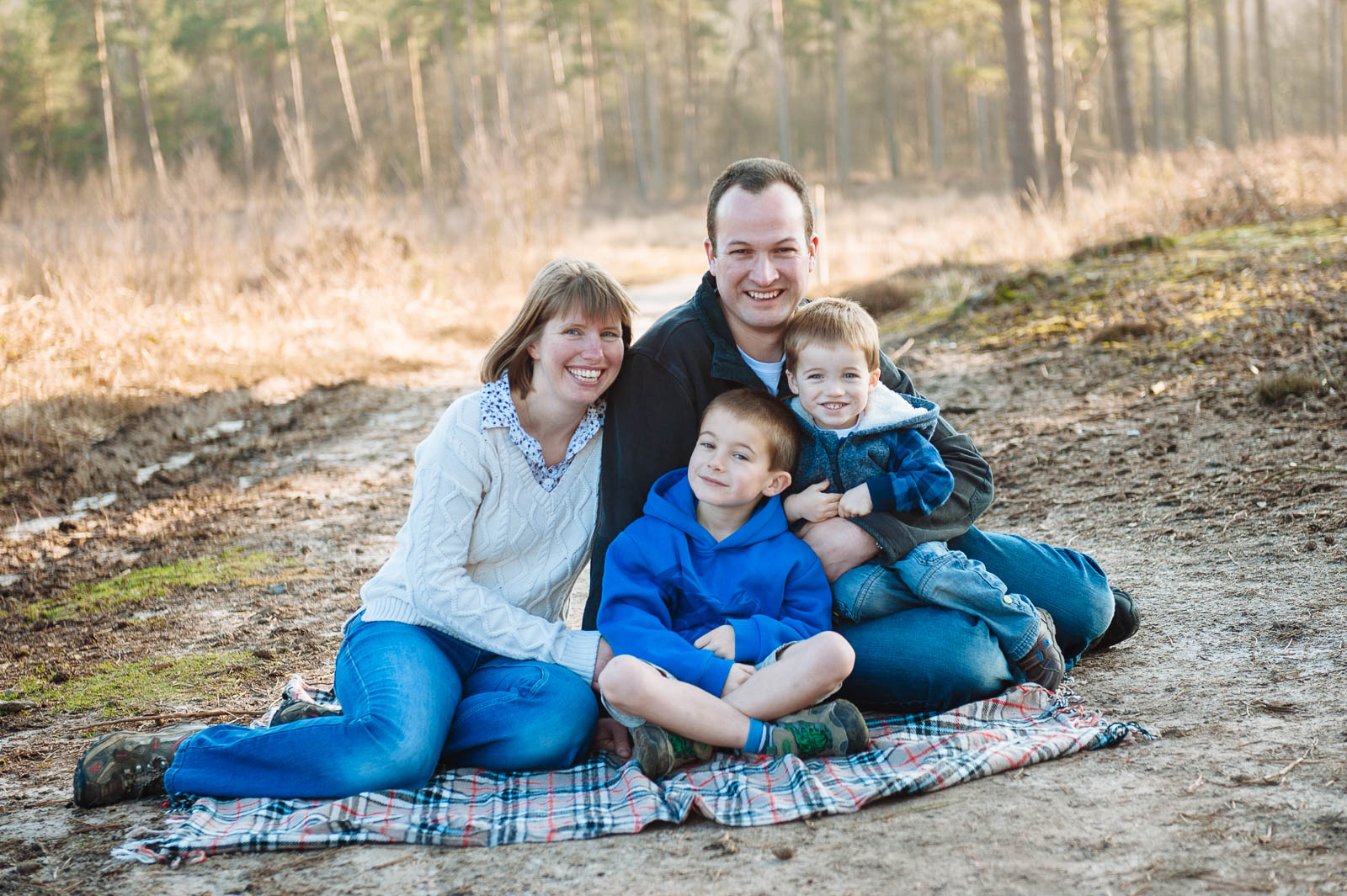 Family pose for photo sitting on a blanket