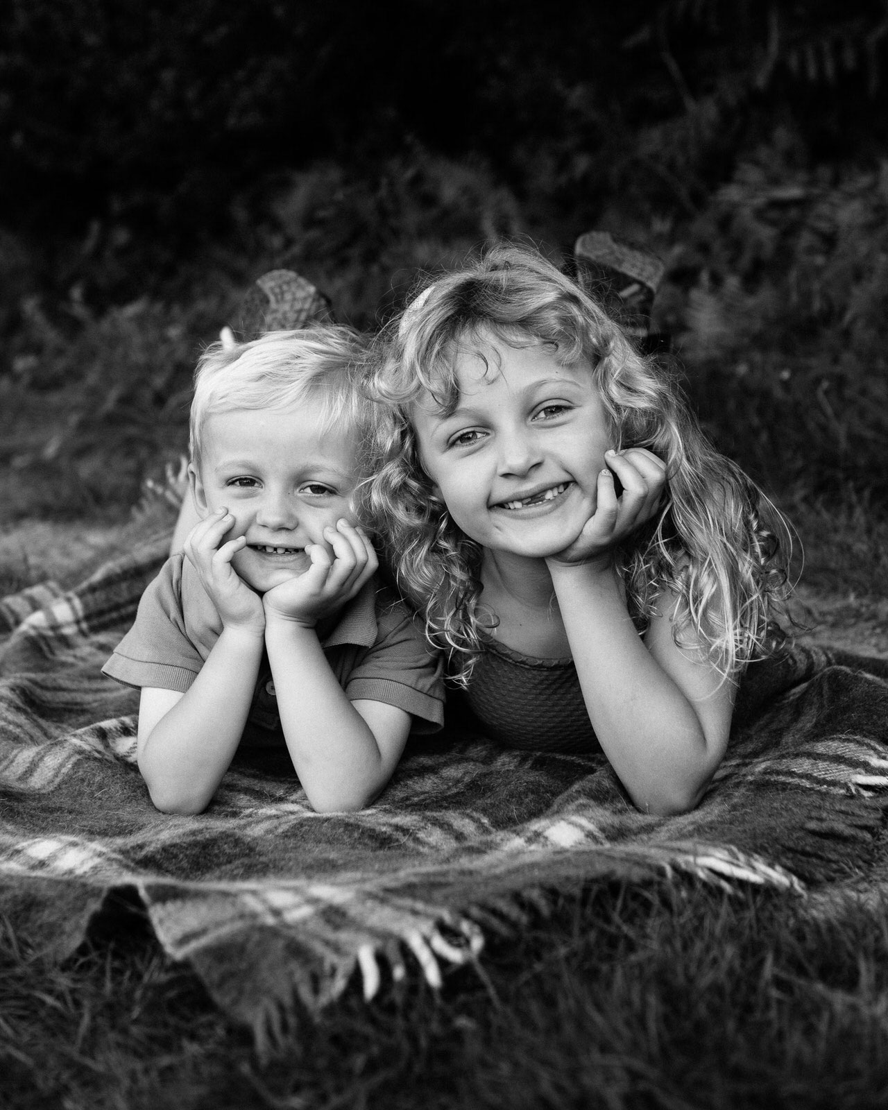 Siblings pose for photo on a blanket