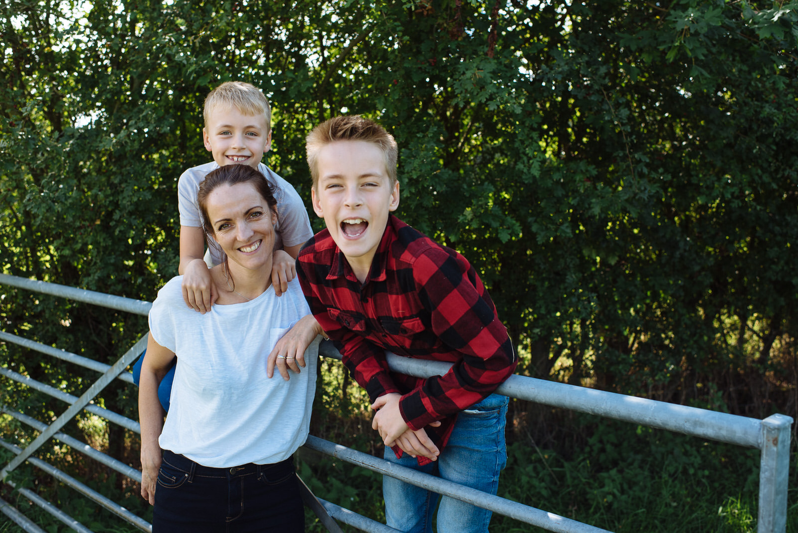 Mum and two sons pose for photo on metal gate