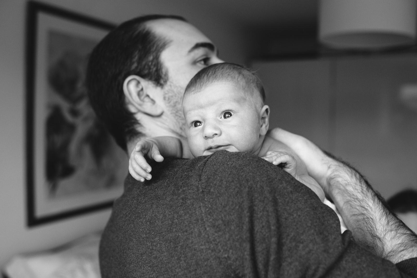 Newborn Baby looks out over dad shoulder - Uckfield newborn photoshoot